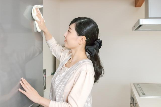 冷蔵庫を拭くエプロン姿の女性