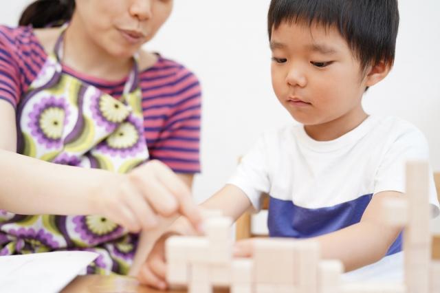 おうち時間に幼児教室の知育ブロックで遊ぶ子供とベビーシッター
